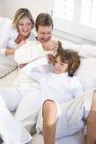 Genitori e figlio che si distendono sul sofà bianco fotografie stock