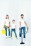 Genitori e piccola figlia con differenti rifornimenti di pulizia fotografie stock