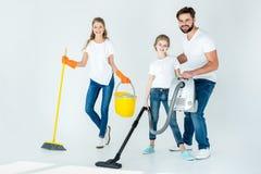Genitori e piccola figlia con differenti rifornimenti di pulizia immagine stock libera da diritti