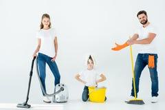 Genitori e piccola figlia con differenti rifornimenti di pulizia immagini stock