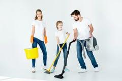 Genitori e piccola figlia con differenti rifornimenti di pulizia fotografia stock libera da diritti