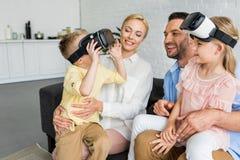 genitori felici che esaminano i bambini svegli che per mezzo delle cuffie avricolari di realtà virtuale fotografia stock libera da diritti