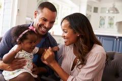 Genitori felici che giocano con la neonata sul ginocchio del ½ s del ¿ del dadï, primo piano Fotografie Stock