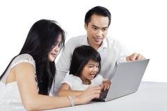 Genitori felici che per mezzo del computer portatile con il loro bambino Fotografia Stock
