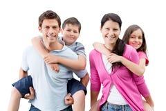 Genitori felici che trasportano sulle spalle i bambini immagini stock libere da diritti