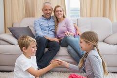 Genitori felici con i loro bambini sul pavimento Fotografia Stock Libera da Diritti