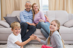 Genitori felici con i loro bambini sul pavimento Fotografia Stock