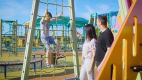 Genitori felici con il figlio che gioca al campo da giuoco del ` s dei bambini stock footage