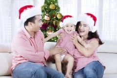 Genitori felici con la loro figlia a tempo di Natale immagini stock