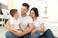 Genitori felici e loro il figlio che si siedono insieme sul pavimento Tempo della famiglia immagini stock