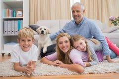 Genitori felici ed i loro bambini sul pavimento con il cucciolo Fotografia Stock