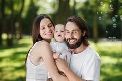 Genitori gloriosi e loro piccola la figlia vestiti nei bei vestiti bianchi immagini stock