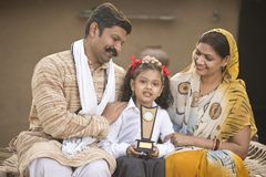 Genitori indiani rurali con il trofeo della tenuta della figlia fotografia stock libera da diritti