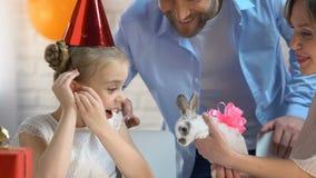 Genitori preoccupantesi che fanno sorpresa a poca ragazza di compleanno che presenta piccolo coniglietto video d archivio