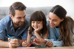 Genitori preoccupantesi sorridenti e disegno sveglio della figlia del bambino con il penc fotografia stock libera da diritti