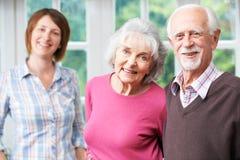 Genitori senior con la figlia adulta a casa Fotografie Stock