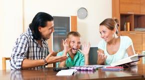 Genitori sorridenti che aiutano con il compito Immagine Stock