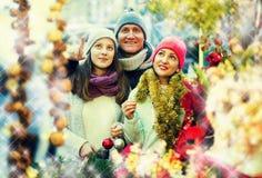 Genitori sorridenti con la figlia del mercato di natale Fotografia Stock