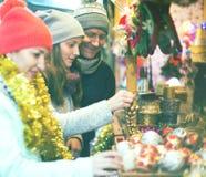 Genitori sorridenti con la figlia del mercato di natale Immagine Stock