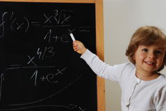 Genius. Beautiful four years old with at blackboard with math formula royalty free stock images