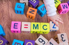Genius baby with high IQ is playing with cubes and writing formulas.  Royalty Free Stock Photos