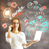 Genius concept. Attractive young woman with laptop in hands on concrete background with eureka exclamation and drawings. Genius concept Royalty Free Stock Photo
