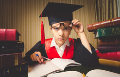 Genius girl in graduation cap looking through eyeglasses at came Royalty Free Stock Photography