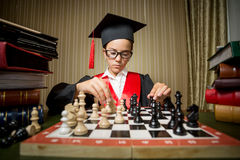 Genius girl in graduation cap playing chess with herself Royalty Free Stock Images