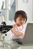 Genius little girl with laptop and microscope Stock Photography