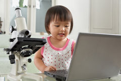 Genius little girl with laptop and microscope Royalty Free Stock Photo