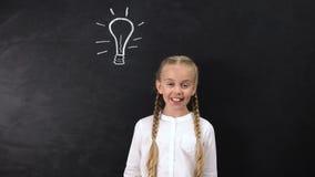 Genius schoolgirl having an idea, pointing finger at light bulb on blackboard