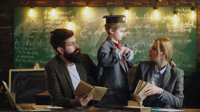 Genius son teach mother and father students. Little child play teacher with woman and man. Family together on chalkboard. With bulbs, ideas. Back to school stock video footage