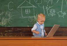 Genius toddler boy use new technology in primary school. Genius child type computer keyboard. Committed to the future.  royalty free stock image