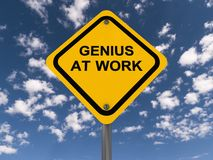 Genius at work sign. A typical yellow road sign with black upper case text saying ' Genius at work ' set against a blue cloudy sky royalty free stock photography