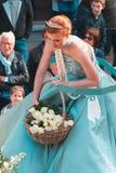 Genk, België - mag 1st 2019: Deelnemers van jaarlijkse o-Parade De koningin van Mei werpt witte rozen aan de menigte stock foto's