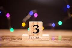 3 gennaio Giorno 3 dell'insieme di gennaio sul calendario di legno su fondo scuro con il bokeh della ghirlanda Orario invernale fotografia stock libera da diritti