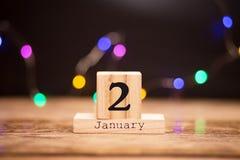 2 gennaio Giorno 2 dell'insieme di gennaio sul calendario di legno su fondo scuro con il bokeh della ghirlanda Orario invernale fotografia stock libera da diritti