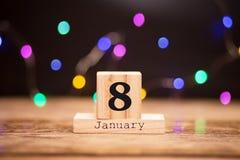 8 gennaio Giorno 8 dell'insieme di gennaio sul calendario di legno su fondo scuro con il bokeh della ghirlanda Orario invernale fotografia stock libera da diritti
