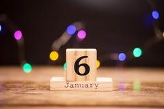 6 gennaio Giorno 6 dell'insieme di gennaio sul calendario di legno su fondo scuro con il bokeh della ghirlanda Orario invernale fotografia stock libera da diritti