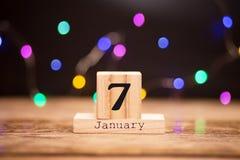 7 gennaio Giorno 7 dell'insieme di gennaio sul calendario di legno su fondo scuro con il bokeh della ghirlanda Orario invernale C fotografia stock libera da diritti