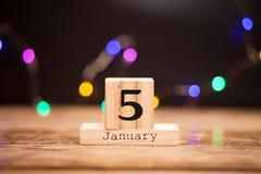 5 gennaio Giorno 5 dell'insieme di gennaio sul calendario di legno su fondo scuro con il bokeh della ghirlanda Orario invernale C fotografia stock