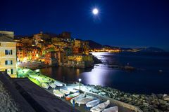 Genoa Boccadasse by night while watching the large moon. This is a fishing village and colorful houses in Genoa, Italy. Genoa Boccadasse by night while watching royalty free stock photos