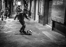 Genoa, Italy - April 21, 2016: Little boy plays soccer with ball. On the narrow alleyways in Genoa, Italy royalty free stock image