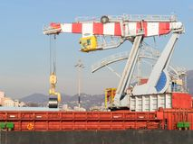 Big port crane loading  steel coil in a cargo ship Royalty Free Stock Image