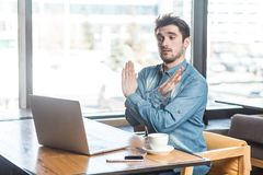Genoeg! Het zijaanzichtportret van waarschuwende agressieve gebaarde jonge freelancer in jeansoverhemd zit in koffie en maakt vid royalty-vrije stock afbeelding