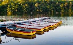 Genoegen het roeien boten die bij de pijler worden vastgelegd stock fotografie