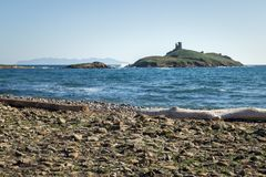 Genoese tower on an island, near a beach in Corsica. royalty free stock image