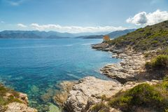 Genoese tower at Mortella near St Florent in Corsica. Ruins of the Genoese tower at Mortella with a turquoise mediterranean sea and rocky coastline of the Desert Stock Image