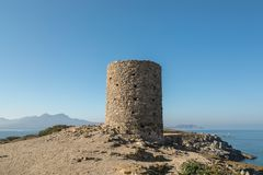 Genoese tower at Punta Spano in the Balagne region of Corsica. Genoese tower at Punta Spano on the coast of the Balagne region of Corsica with Revellata in the royalty free stock photos