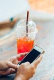 Genom att använda den smarta telefonen och att dricka te Arkivfoto